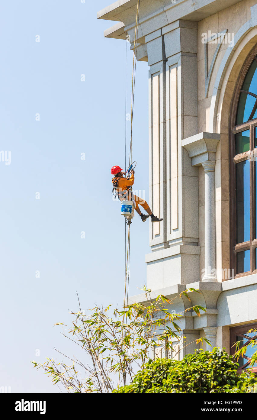 Window cleaner wearing orange overalls and red helmet, suspended from harness and ropes cleaning windows in Chennai, Stock Photo