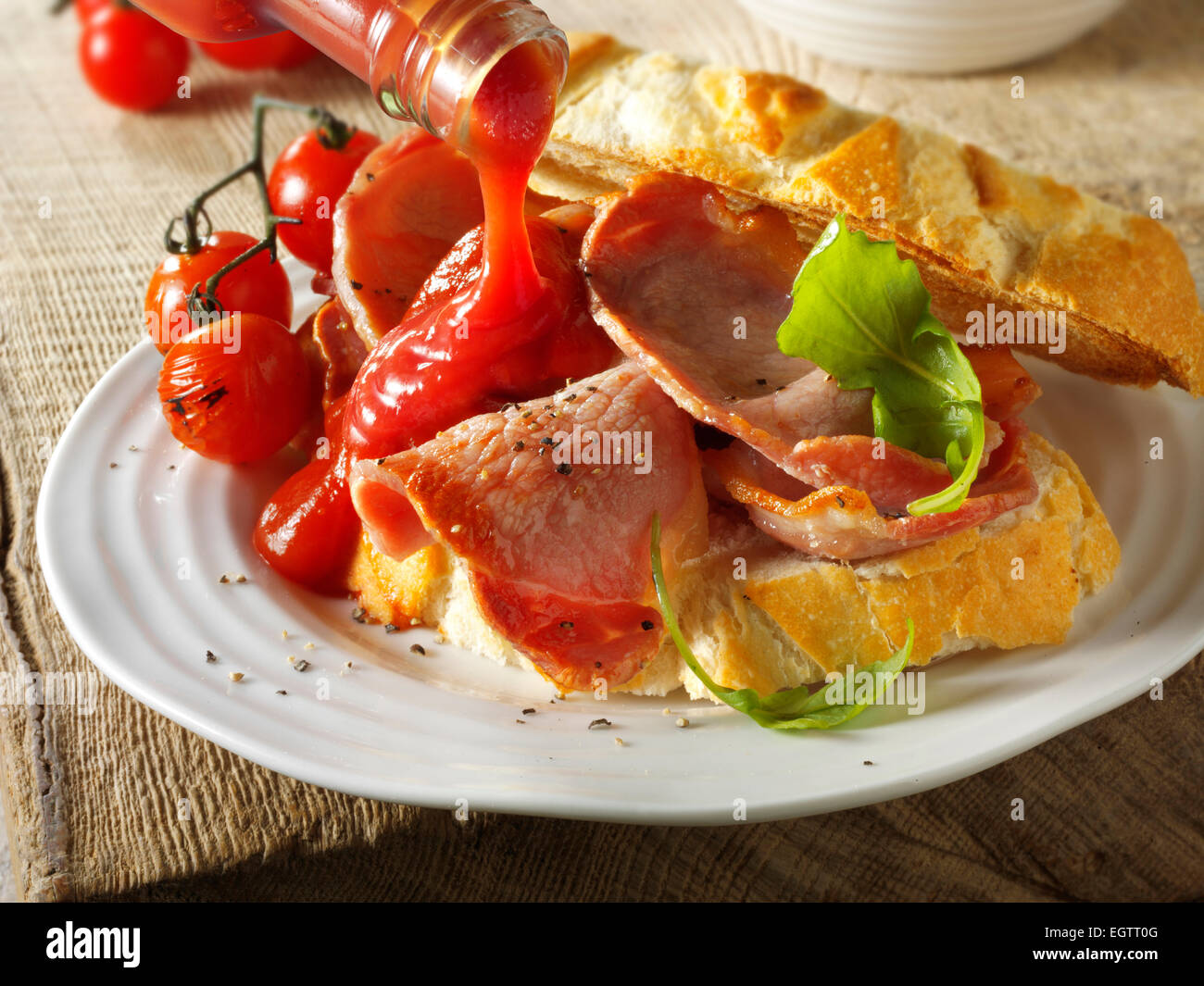 Bacon sandwich with tomato ketchup being added - Stock Image