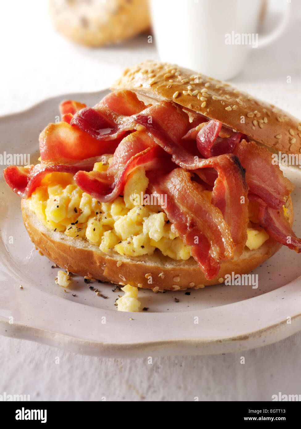 Crispy backon and scrambled eggs on a bagel - Stock Image
