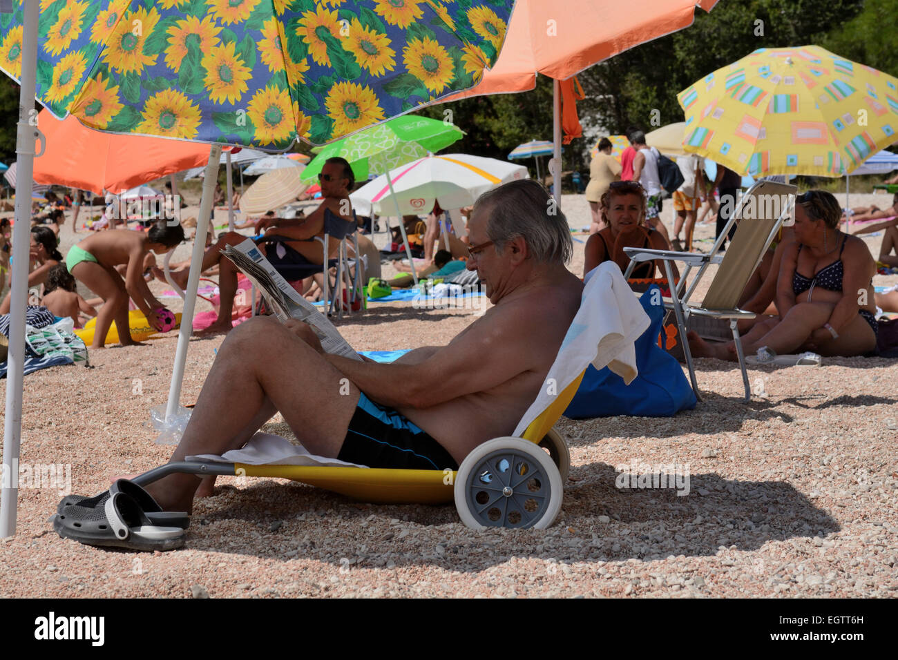 Italian Tourist in Sardinia sat on beach reading the paper - Stock Image