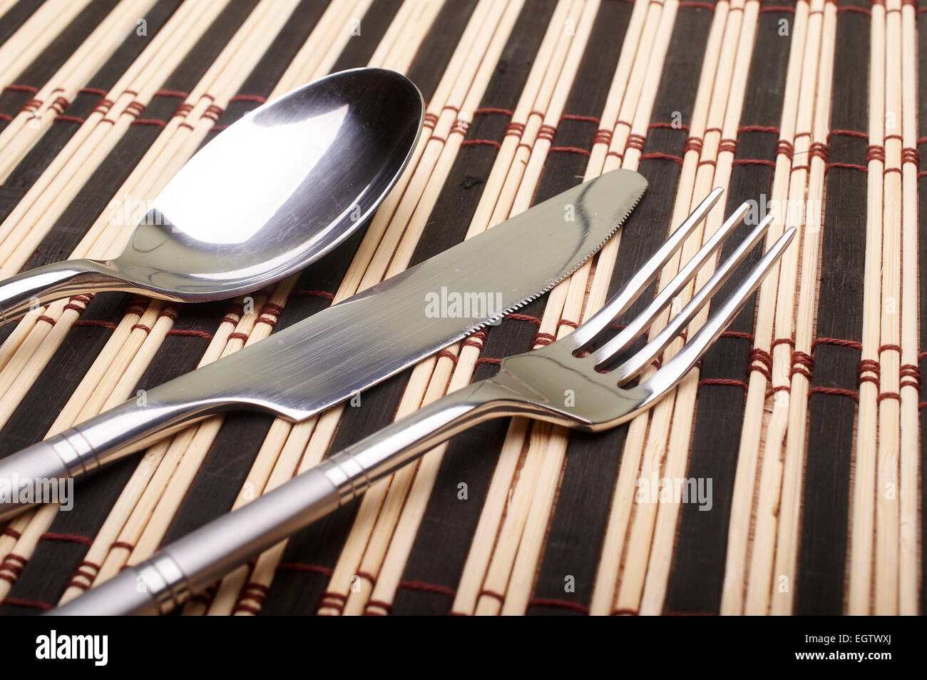 Cutlery on placemats Stock Photo