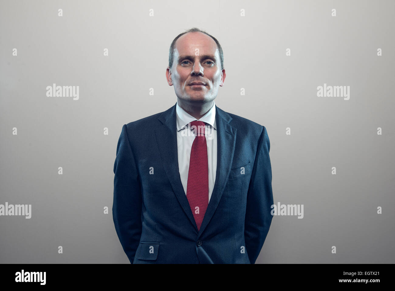 environmental portrait of businessman executive director in a suit lit in a creative way to imply technology & advancement Stock Photo