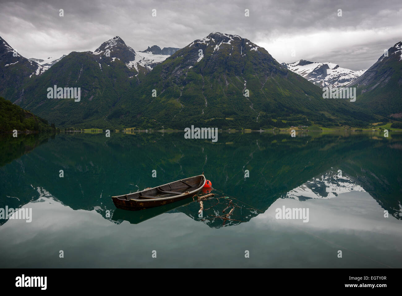 An old row boat in the still water of Oppstrynsvatnet with reflection of the mountains in a Norwegian landscape - Stock Image