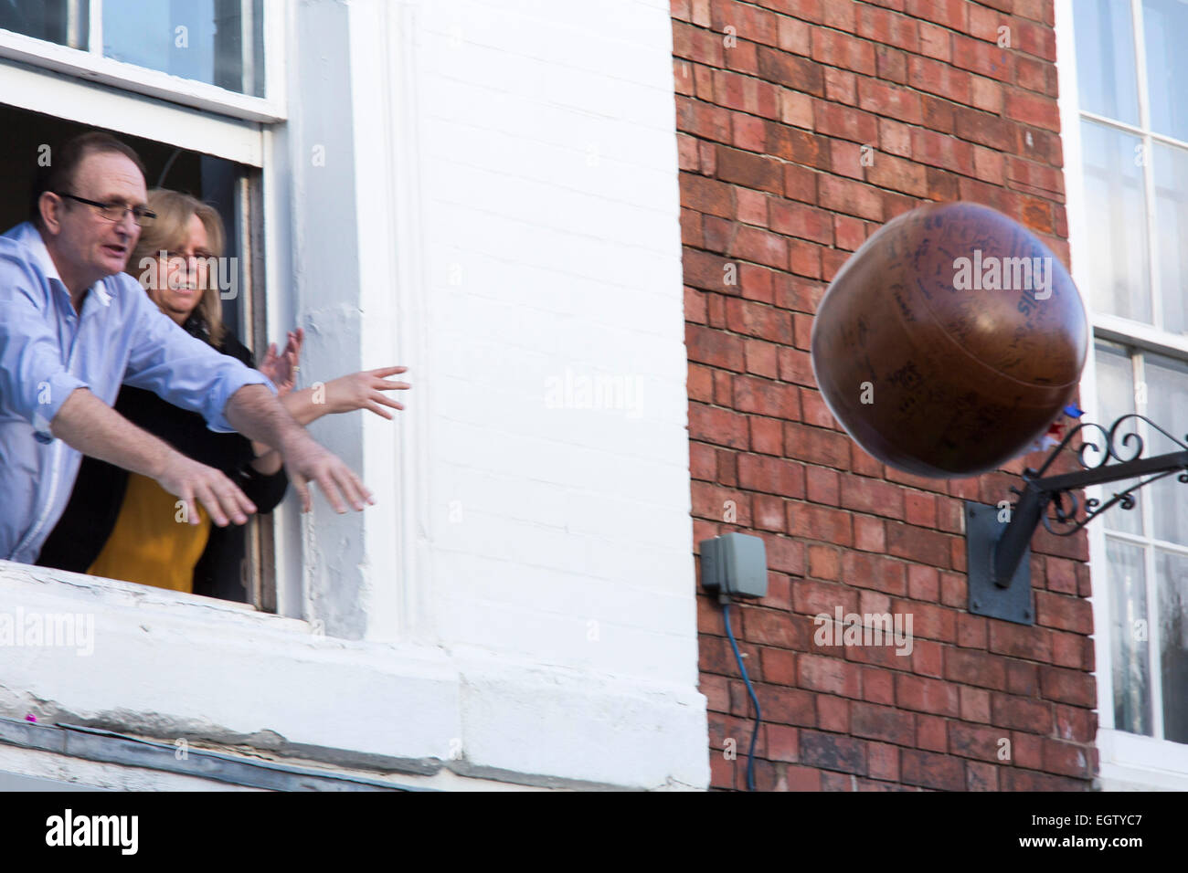 Atherstone Ball Game. Two teams kick a leather ball up and down Long Street, Atherstone. The ball is thrown out - Stock Image