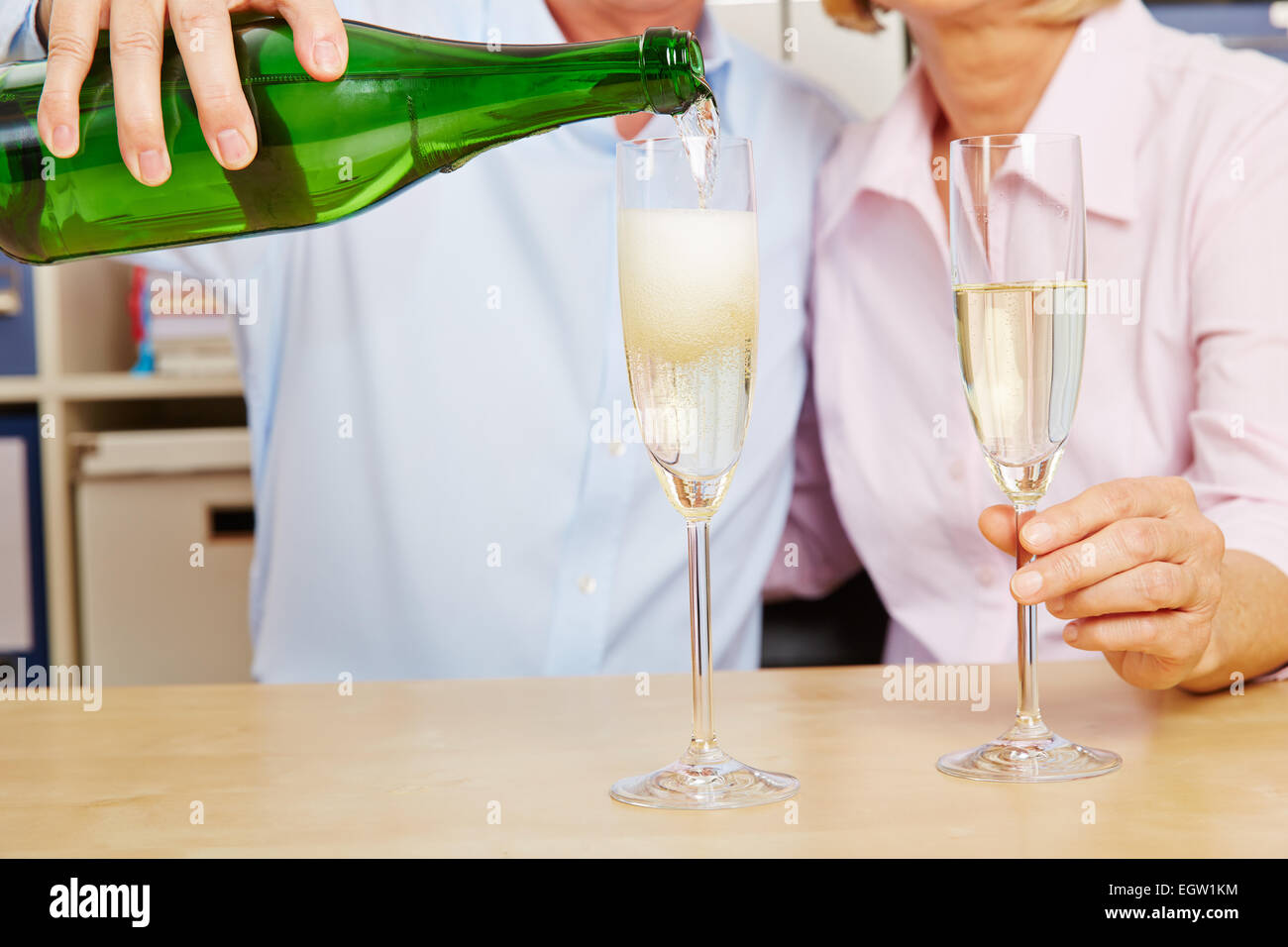 Old couple pouring champagne in glass for New Year's Eve - Stock Image