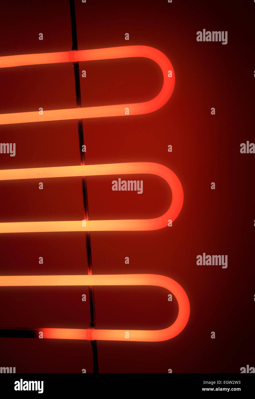 Electrical heating element of an electrical barbeque grill glowing in the dark. - Stock Image