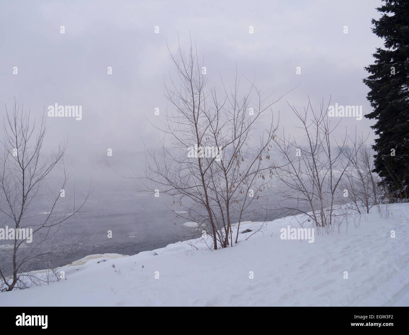 Fog on the river on an overcast day in winter - Stock Image