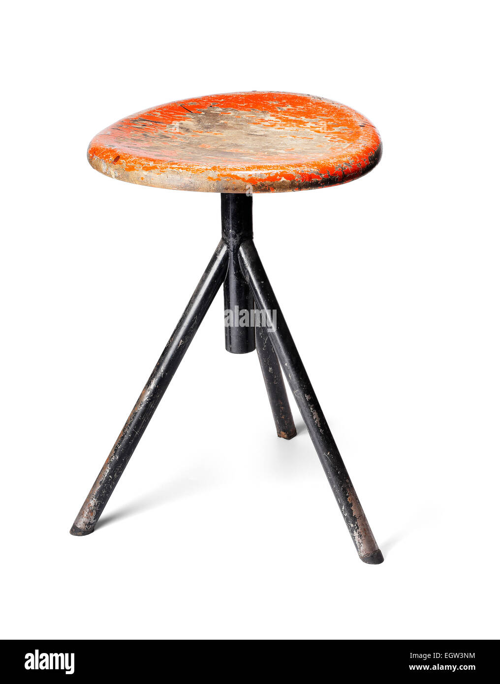 Old thee-legged stool from a workshop. Isolated on white with natural shadows. - Stock Image