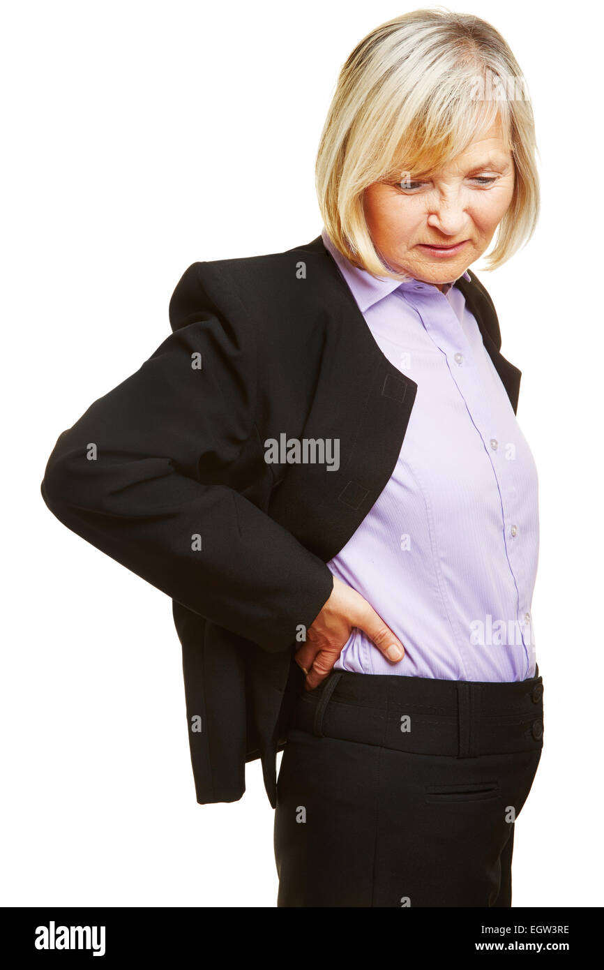 Old business woman having back pain and holding her aching back - Stock Image