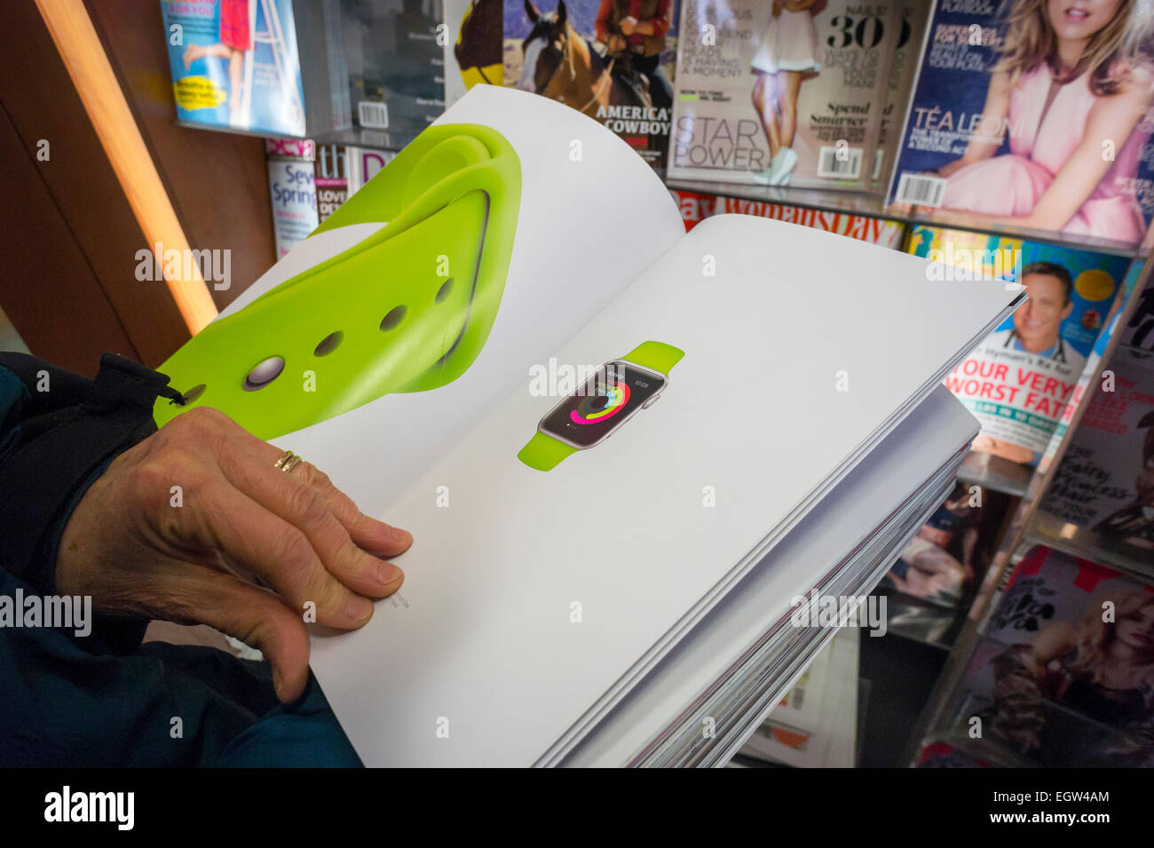 A shopper reviews a 12 page advertisement for the Apple Watch in the March issue of Vogue magazine at a newsstand - Stock Image