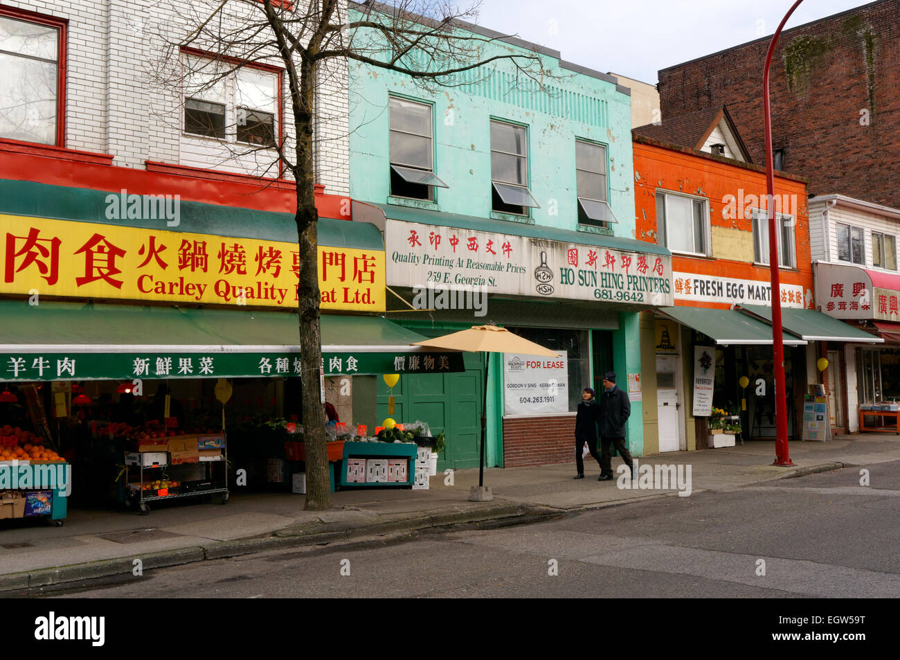 A couple walking past colourful storefronts on Keefer Street in Chinatown, Vancouver, BC, Canada - Stock Image