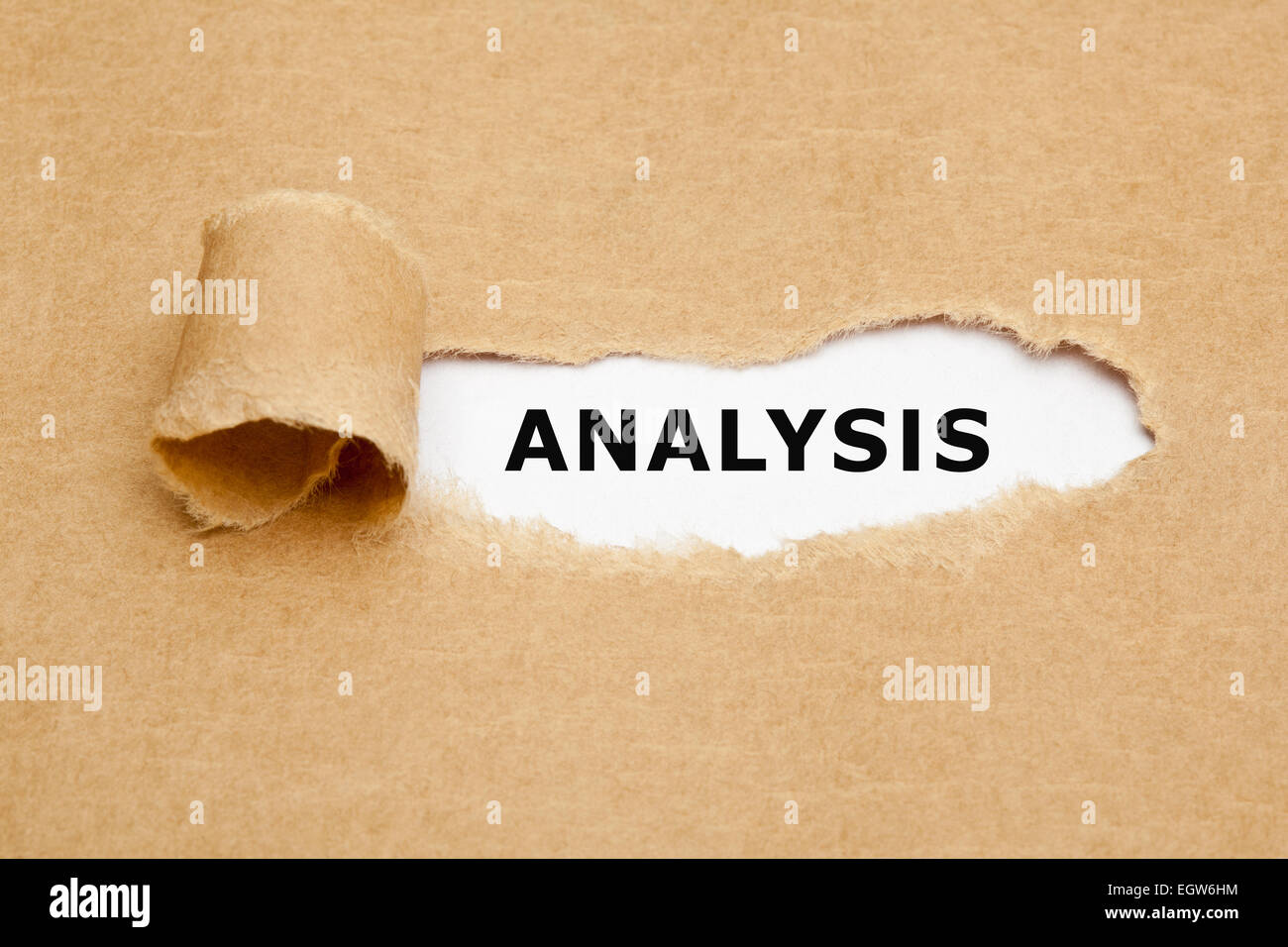 Analysis appearing behind torn brown paper. Stock Photo