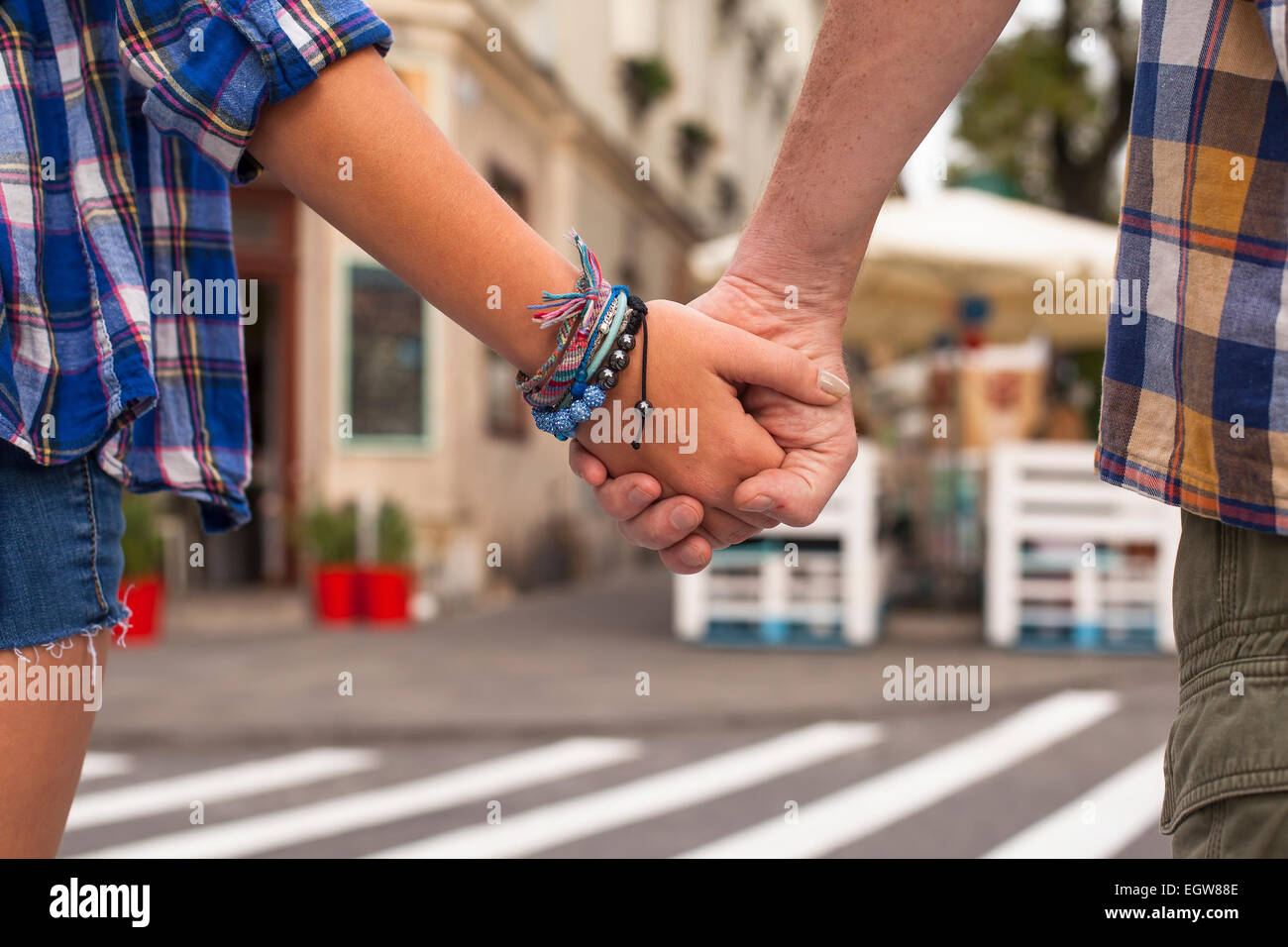 Close-up of the holding hands of a young couple in a summer town. Stock Photo