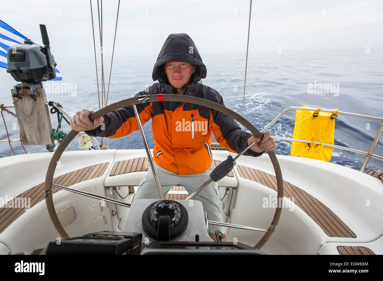 Young man skipper in the sea at the helm of a sailing yacht. Stock Photo