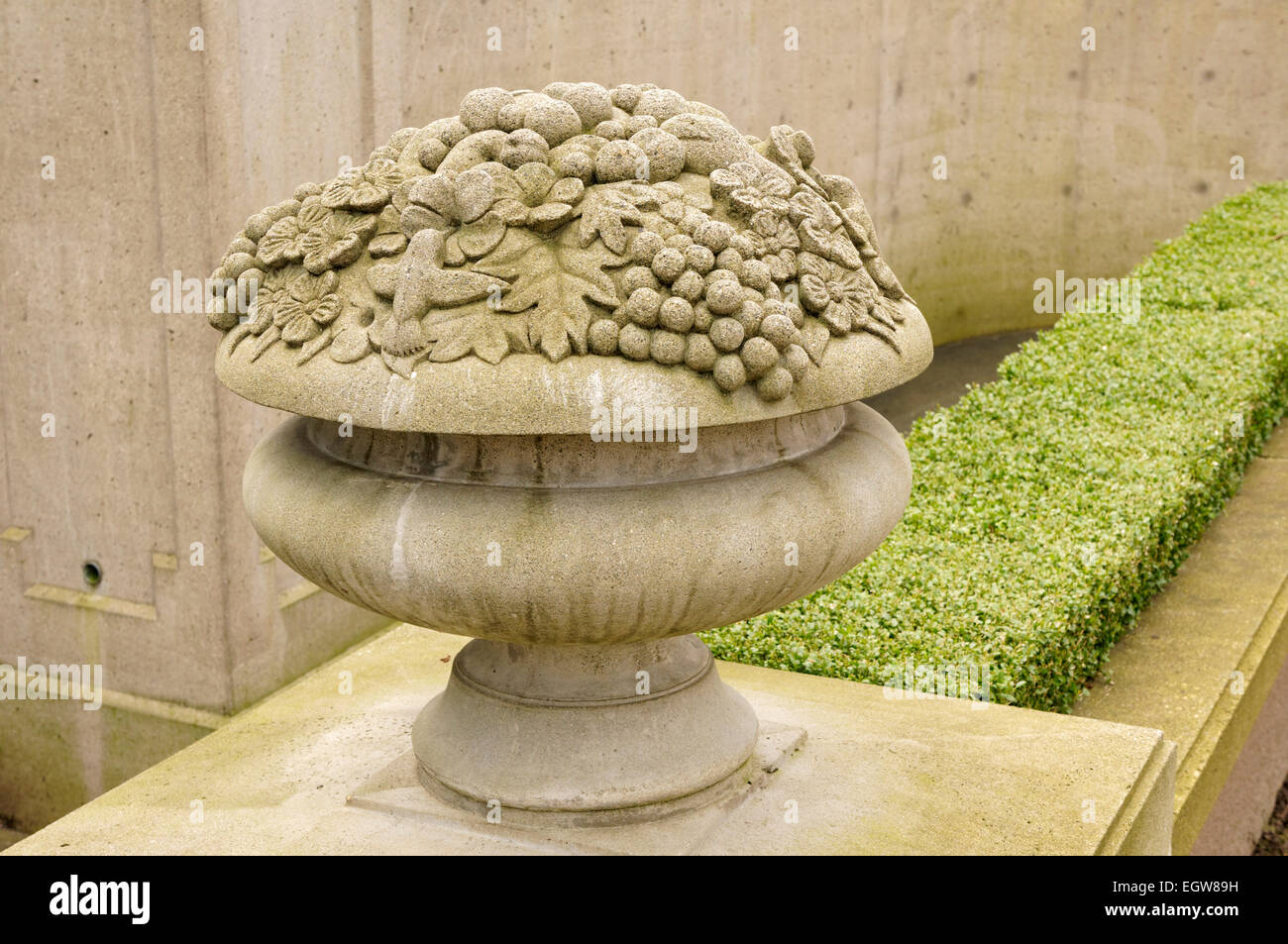 Stone sculpture of a chalice filled with fruit - Stock Image