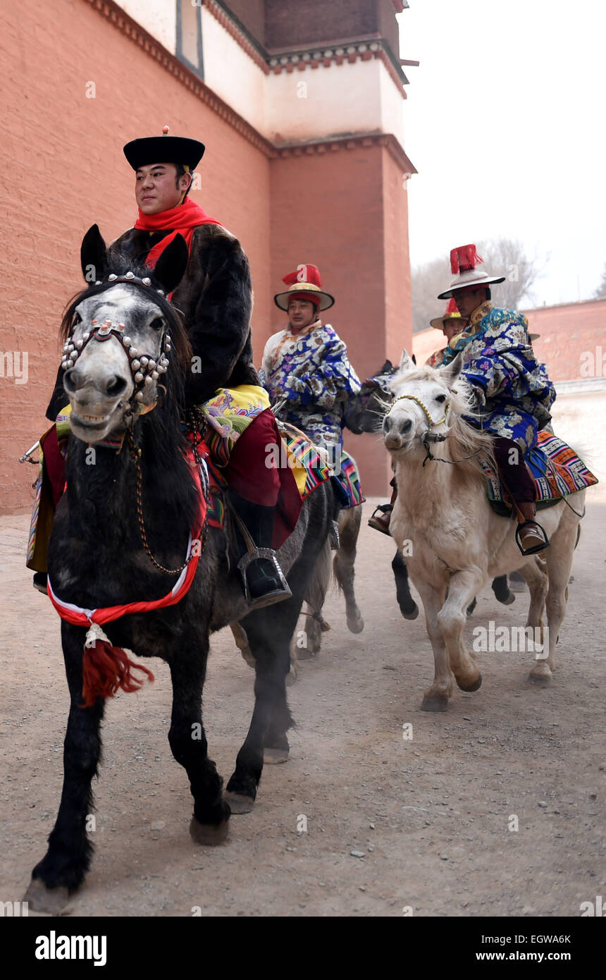 Xiahe, China's Gansu Province. 3rd Mar, 2015. Cavalries wait for lamas to carry a gigantic Buddha tangka (Tibetan - Stock Image