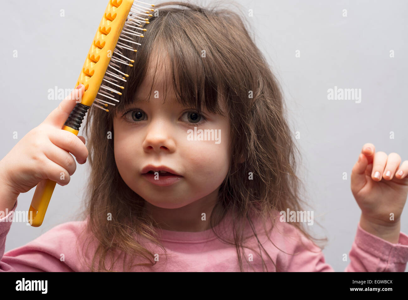 2-year old girl brushing her hair