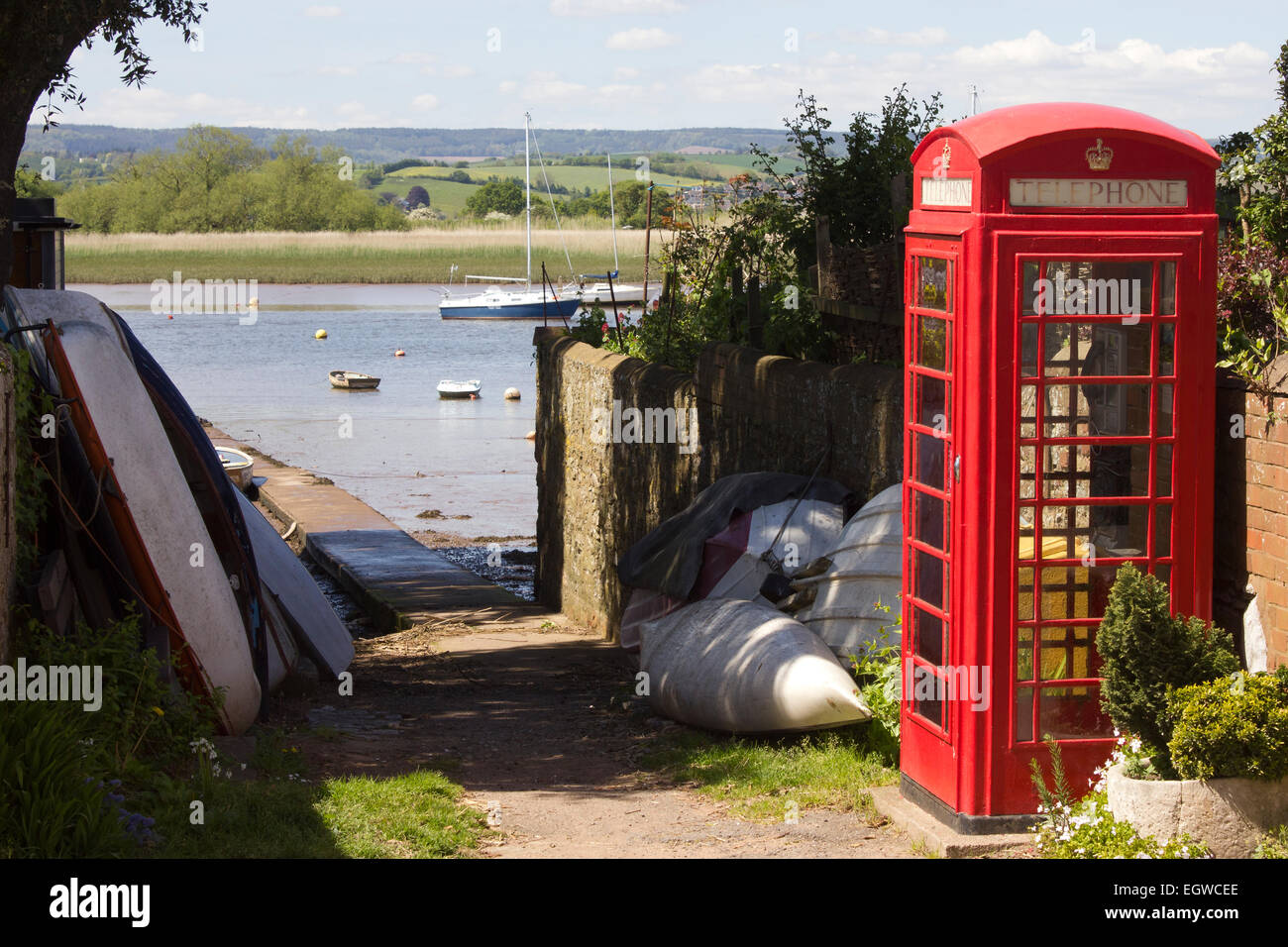 British red phone box next to the River Exe estuary in the village of Topsham, Devon UK, with views across the river. - Stock Image