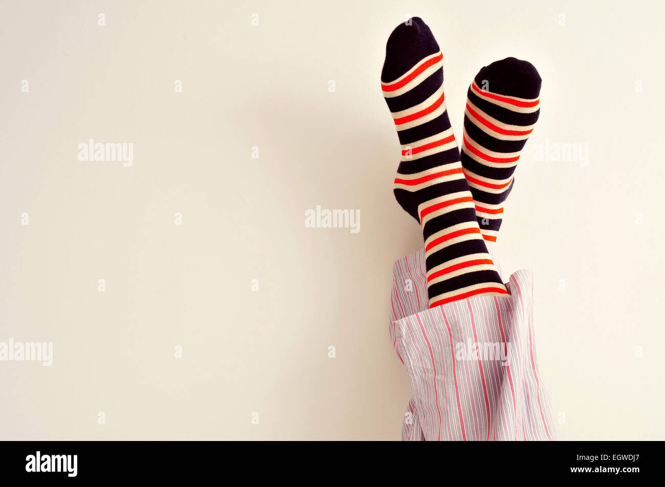 closeup of a young man in pajamas with his feet against the wall - Stock Image