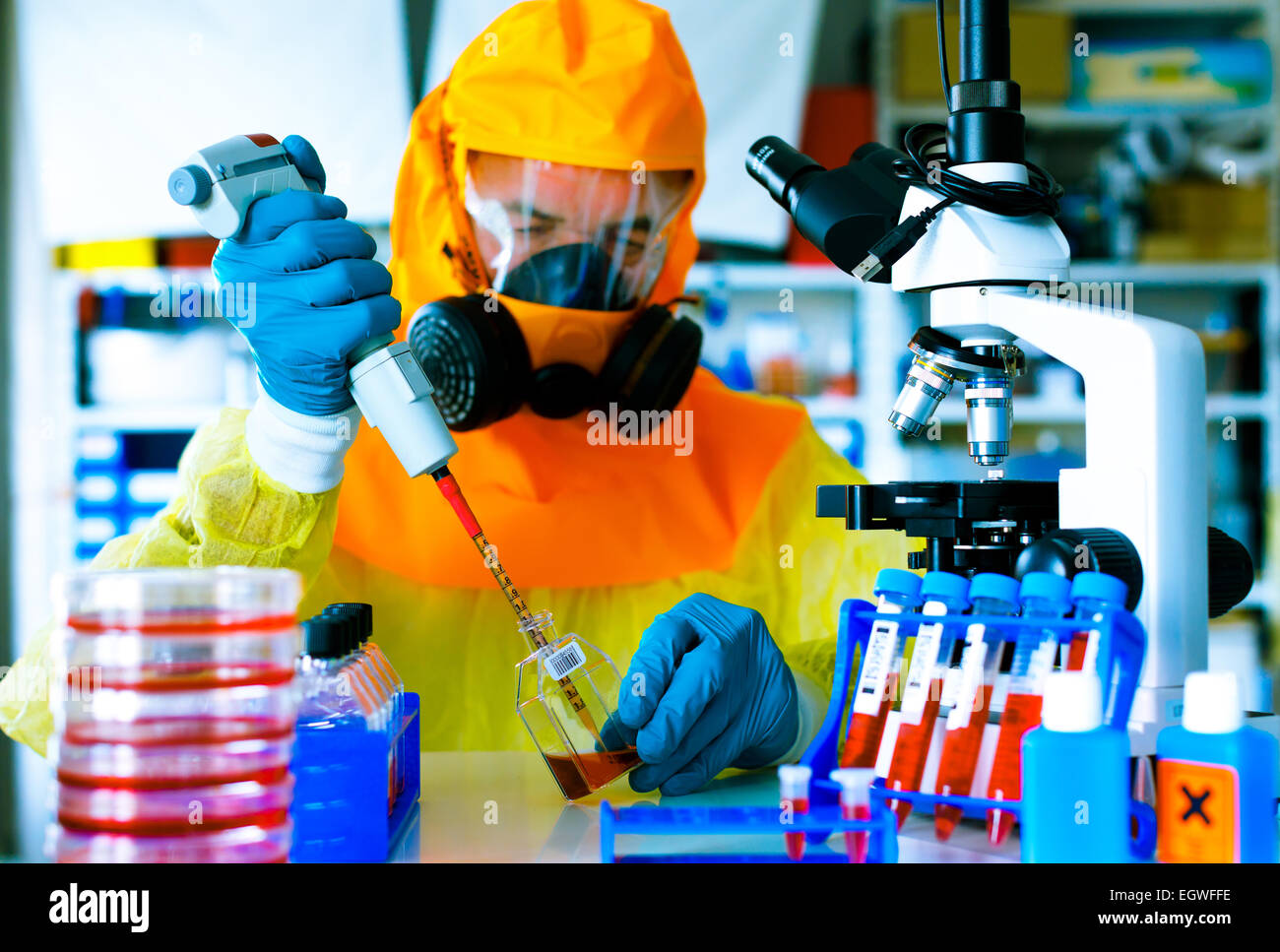 test a vaccine against Ebola infection, a scientist in protective suit with a pipette and a microscope in a laboratory - Stock Image