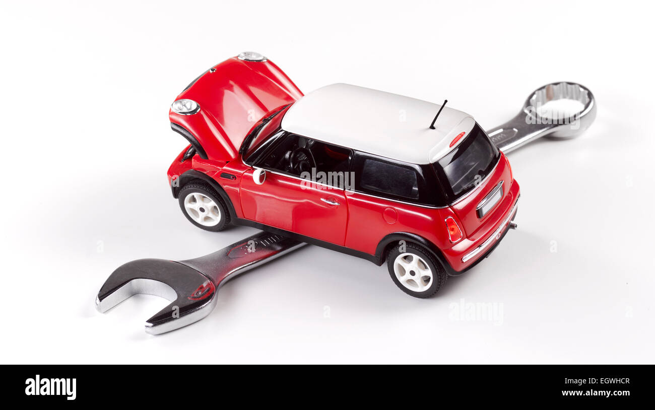the cost of maintaining a car, cost of motoring, red car shot from above on white with spanner - Stock Image