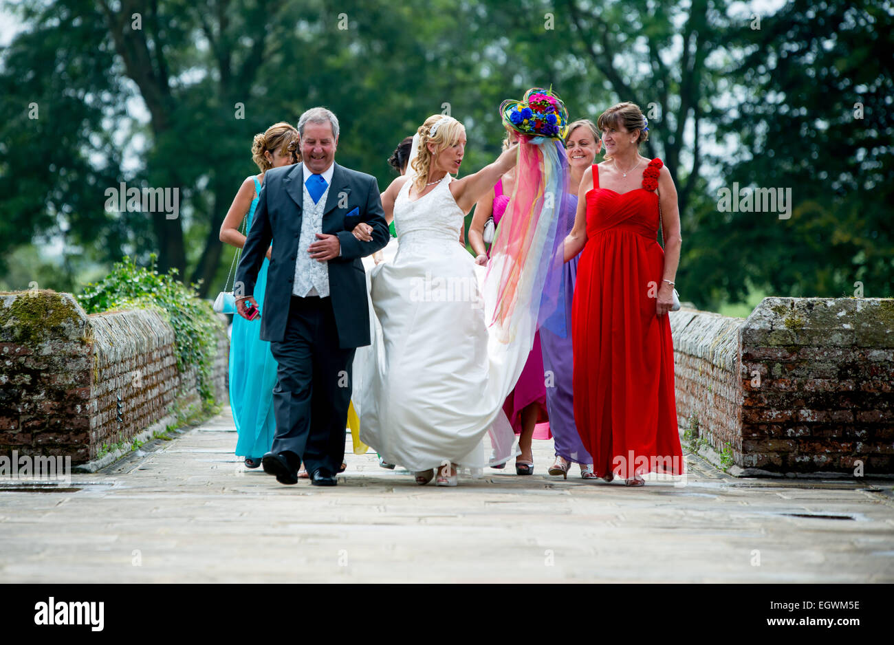 A bride dances excitedly as she walks towards her wedding ceremony with father of the bride and bridesmaids. Stock Photo