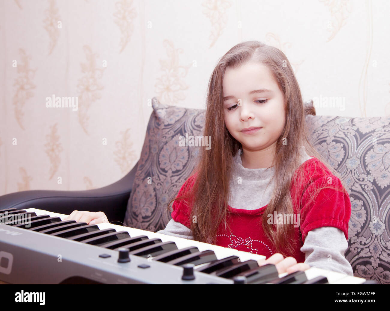 girl playing on a synthesizer - Stock Image