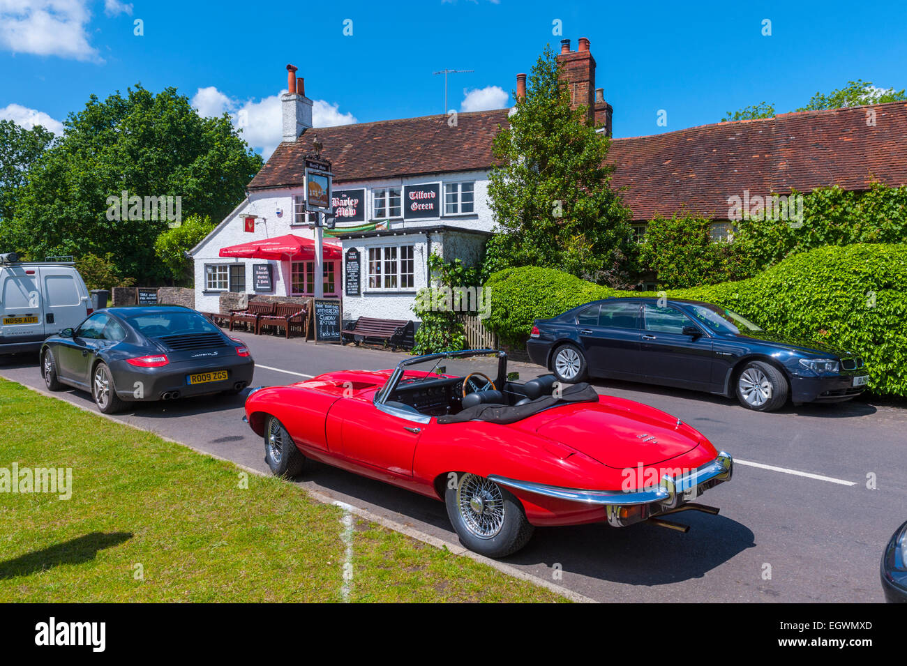 E Type jag parked outide of the Barley mow pub Tilford surrey. - Stock Image