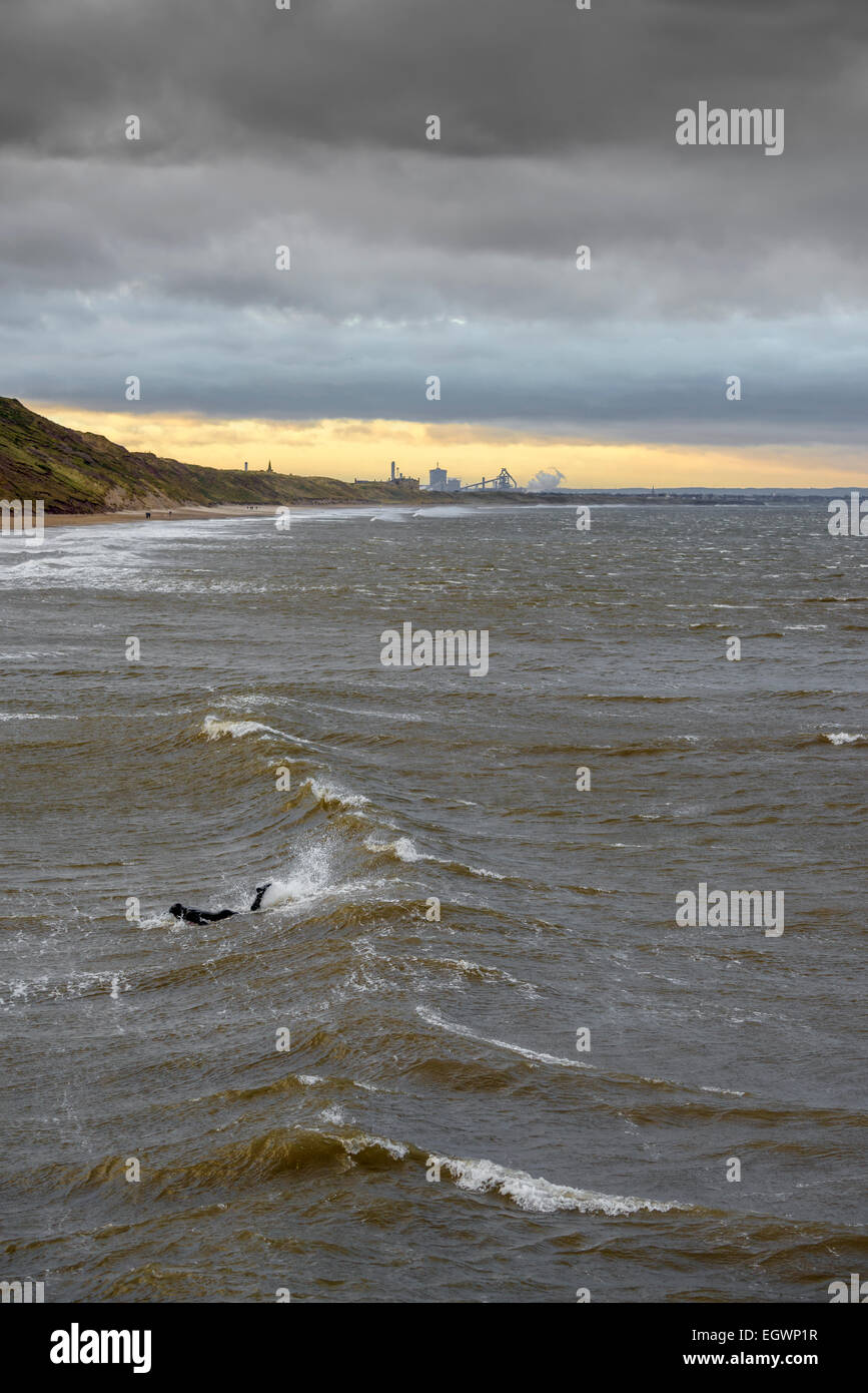 Lone surfer kicks to catch a wave on a cold Winter's day at Saltburn-by-the-Sea, North East UK with a sunset - Stock Image
