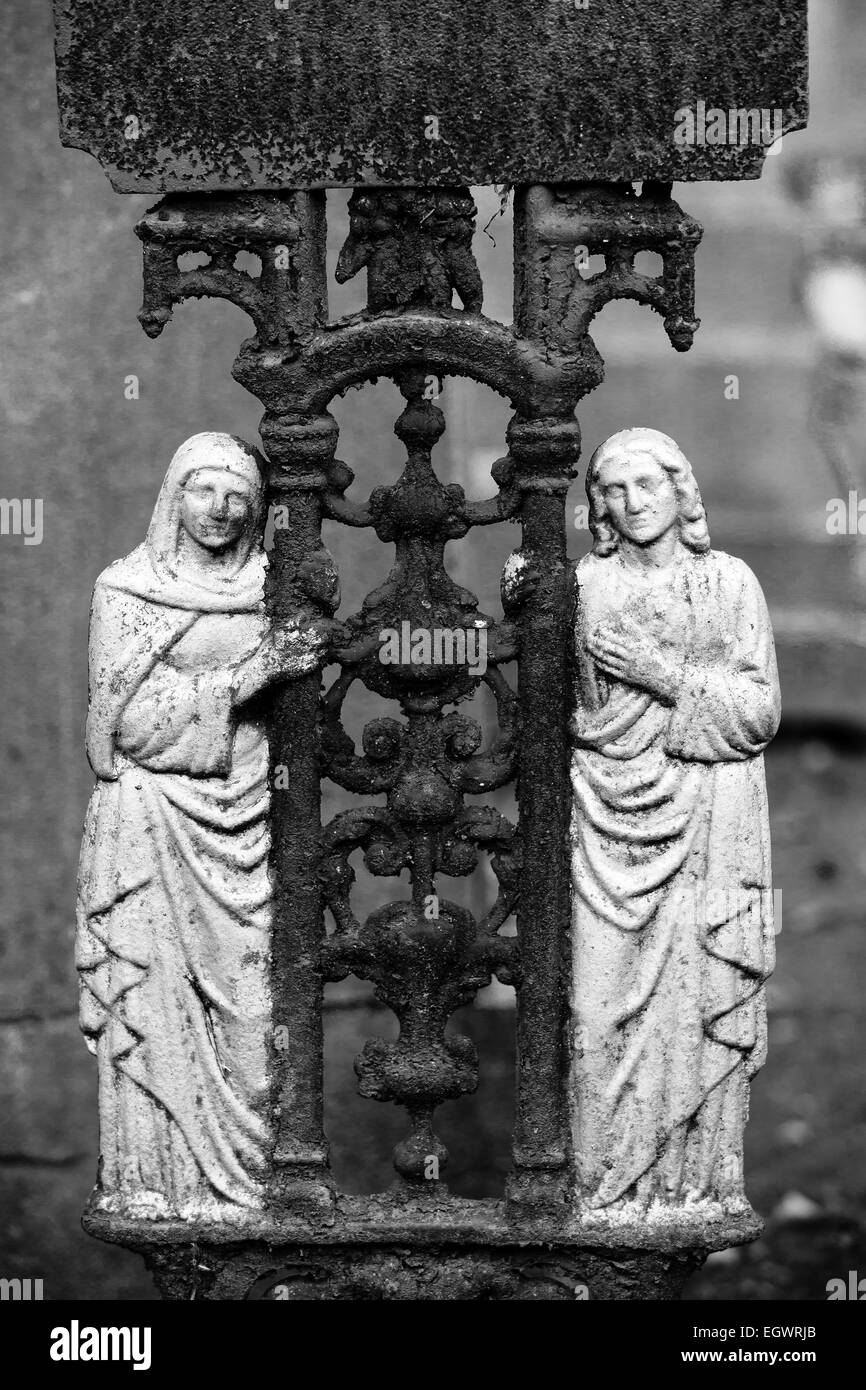 Detail of a old iron cross at the cemetery Hasselt Monochrome, 2 saints holding the crucifix - Stock Image