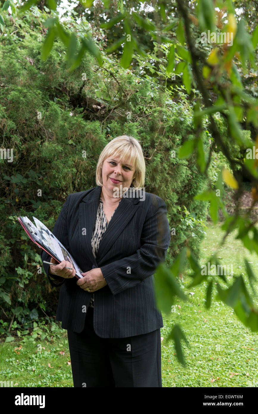 a professional business woman / wedding planner in a business suit stands with a file / folder in the grounds of - Stock Image