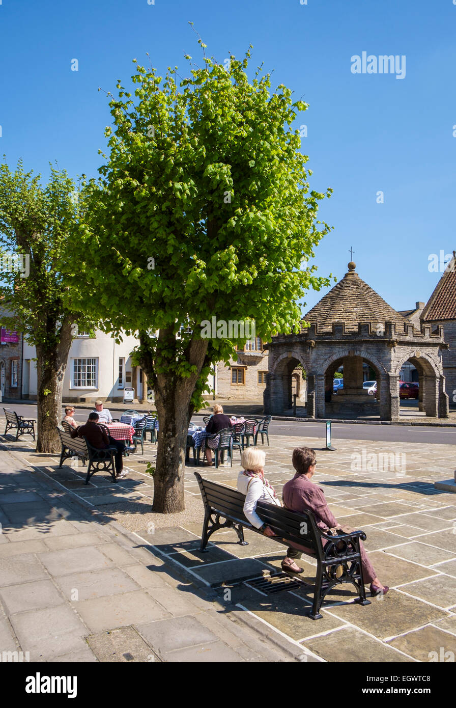 Somerton, a beautiful old small market town in Somerset, England, UK with market cross and people sitting on a bench - Stock Image