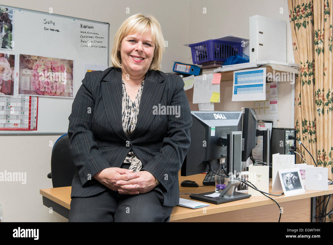 a business administrator office manager by her desk in a busy office environment managing aspects of a hotel and - Stock Image