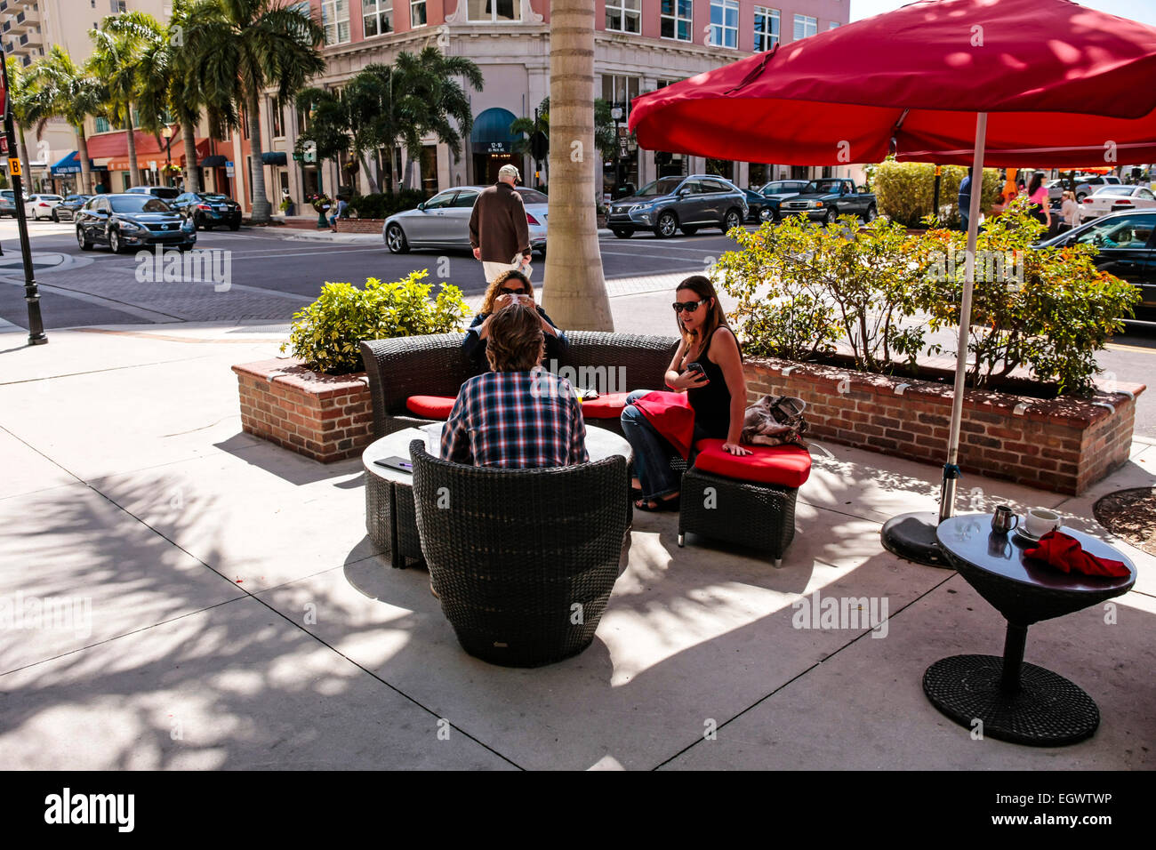 People relaxing outside in comfy chairs at a cafe/restaurant in downtown Sarasota during February - Stock Image