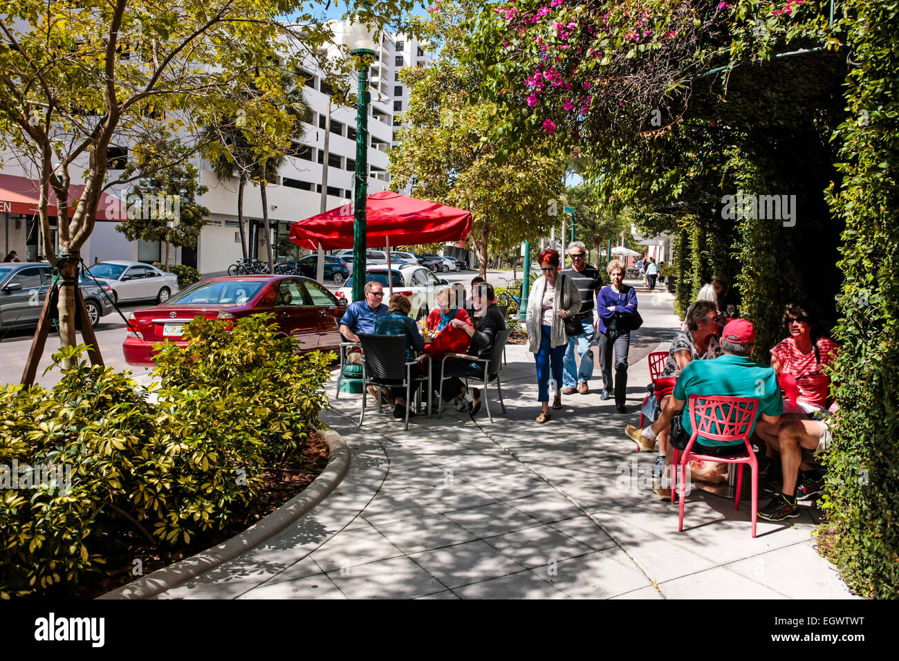 People relaxing, taking an early brunch outside in comfy chairs at a cafe/restaurant in downtown Sarasota during - Stock Image