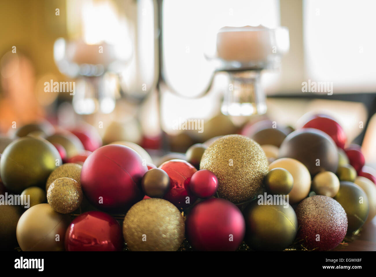 A table laid for a celebration meal. Christmas ornaments, decorations and a candle in a candle holder. - Stock Image