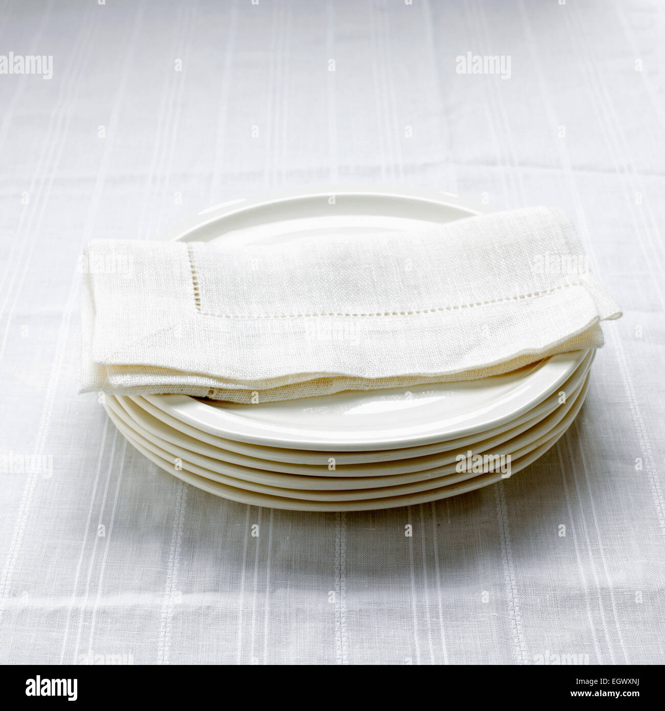 Stack of white plates on a white cloth with a white serviette - Stock Image