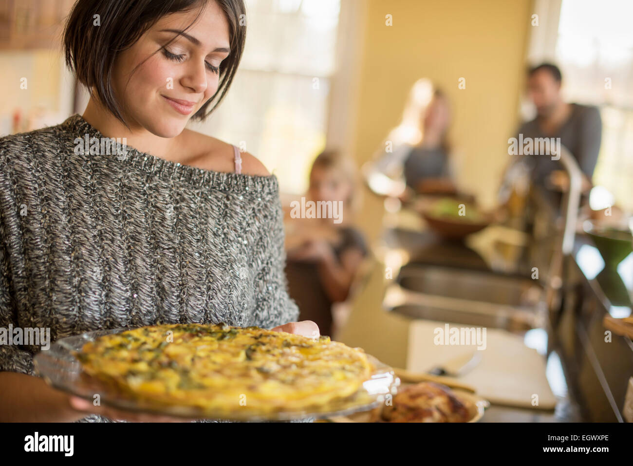A woman carrying prepared food to the table. - Stock Image