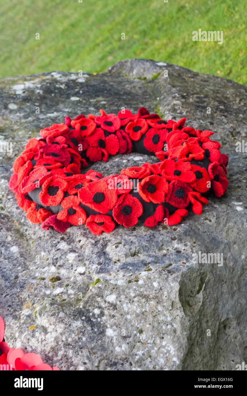 knitted poppy wreath on memorial stone at Hythe, Hampshire, England UK - Stock Image