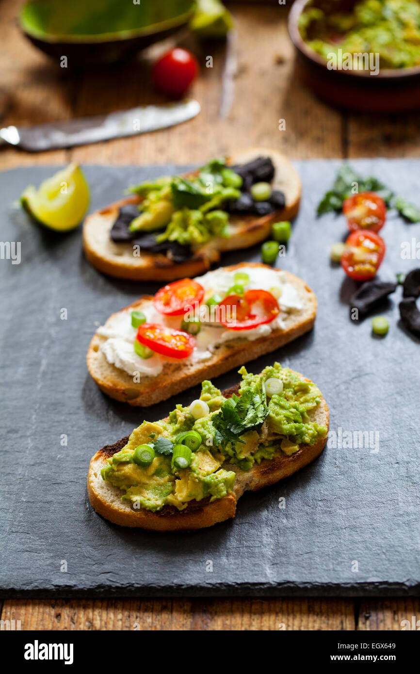 Canapes with avocado spread, goat cheese and black garlic - Stock Image