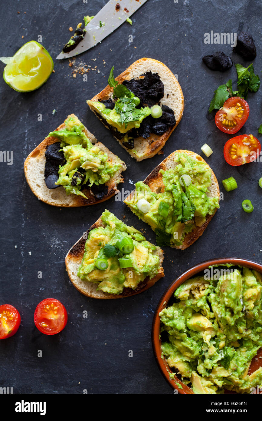 Canapes with avocado spread and black garlic - Stock Image