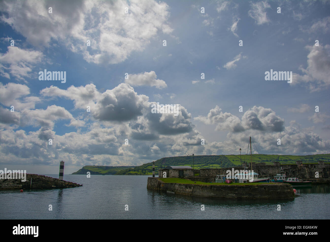 A small harbor at the coast of Ireland on a partly cloudy day - Stock Image