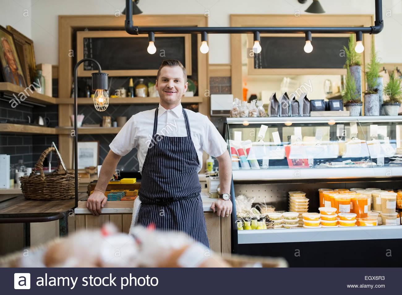 Portrait of confident market owner wearing apron - Stock Image