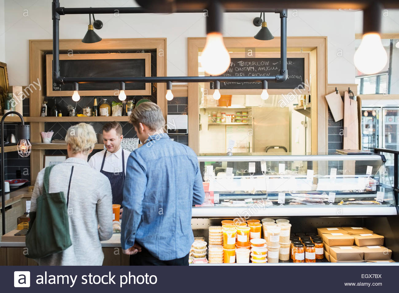 Market worker assisting customers at front counter - Stock Image