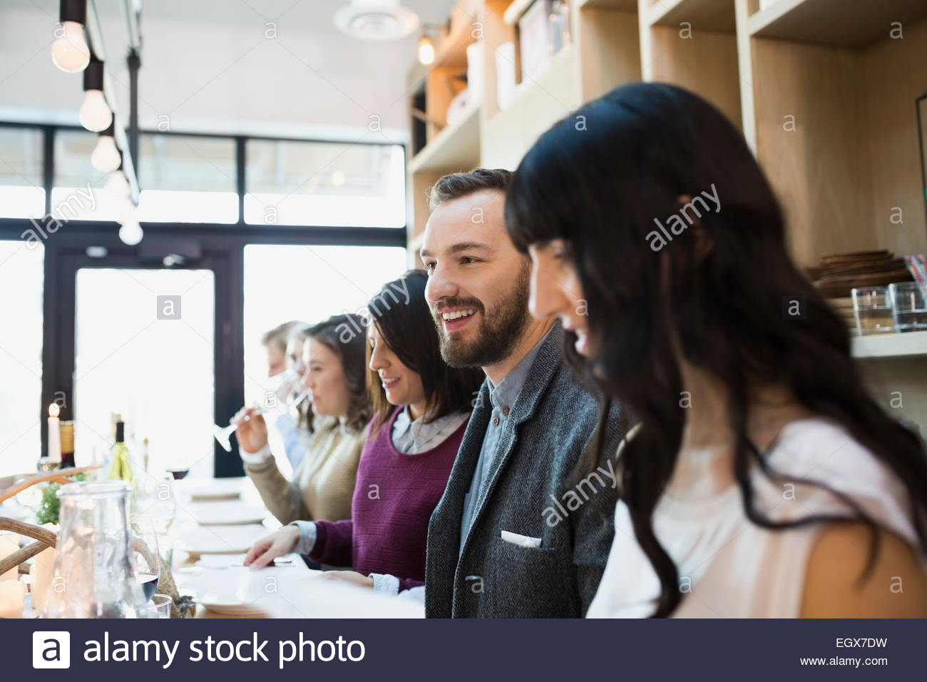 Friends sitting at communal table in restaurant - Stock Image