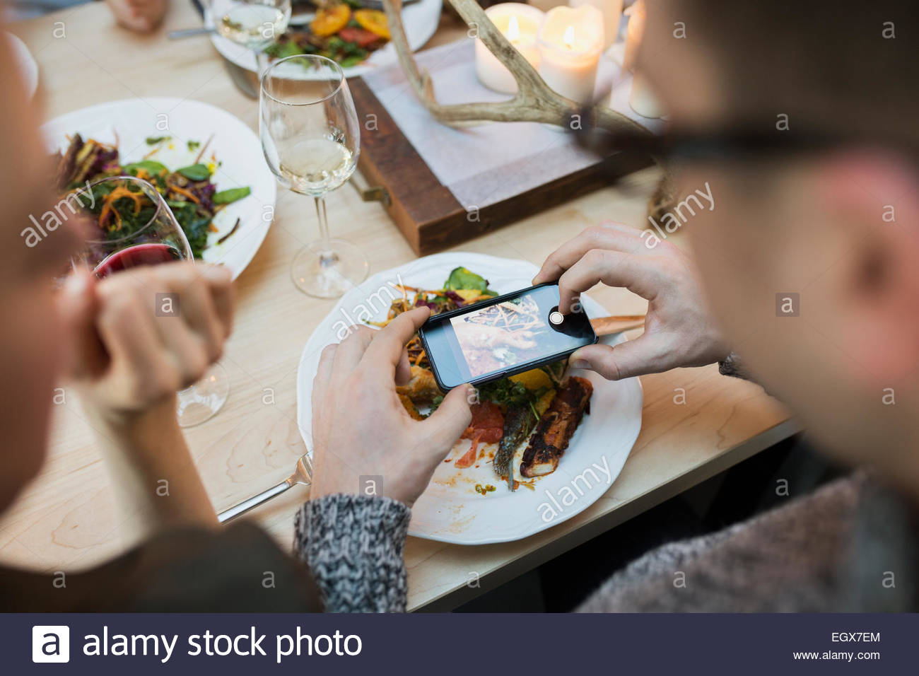 Man photographing plate of food at restaurant table - Stock Image