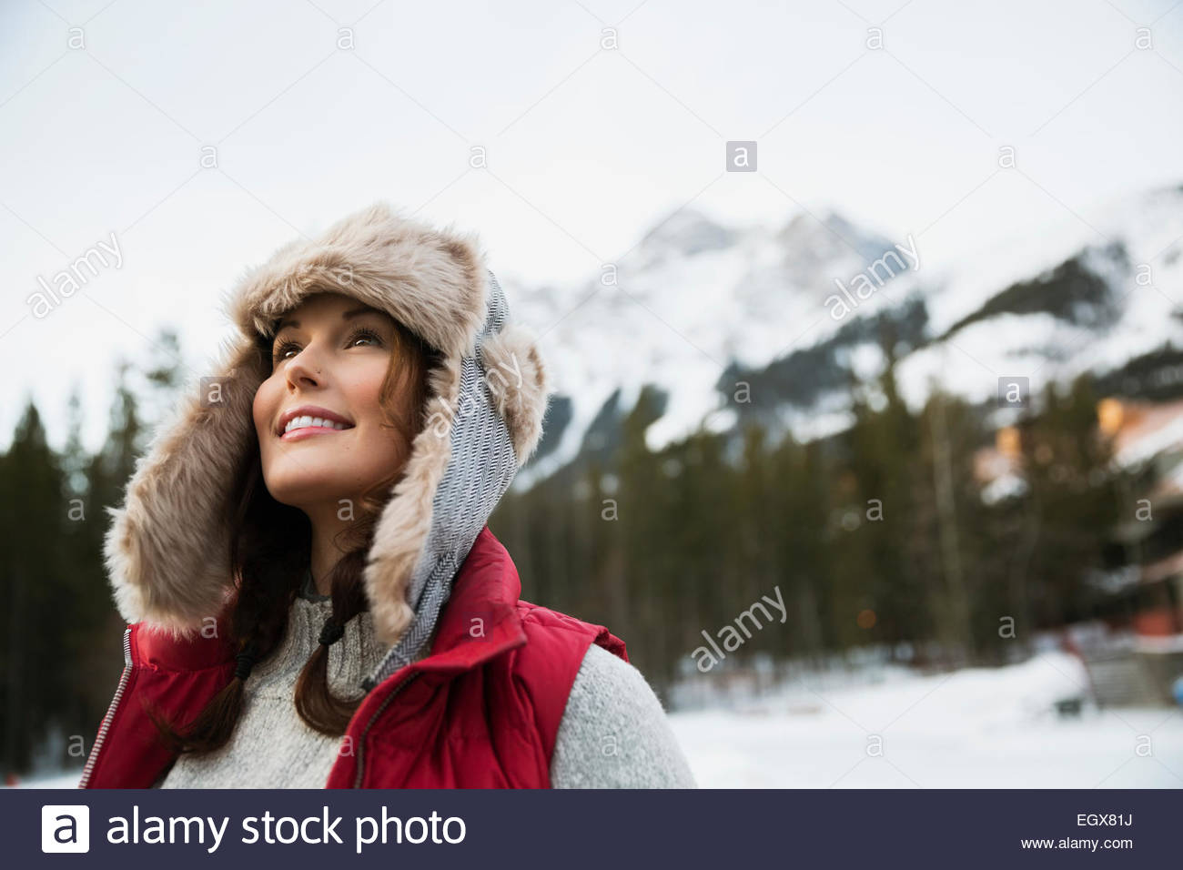 Curious woman looking up below snowy mountains - Stock Image