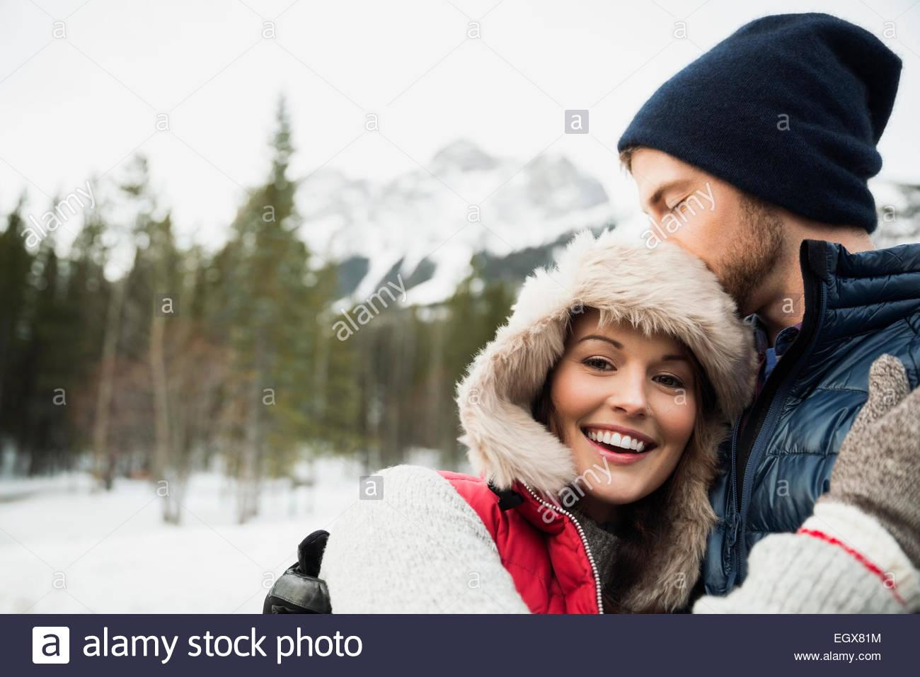 Couple hugging below snowy mountain - Stock Image