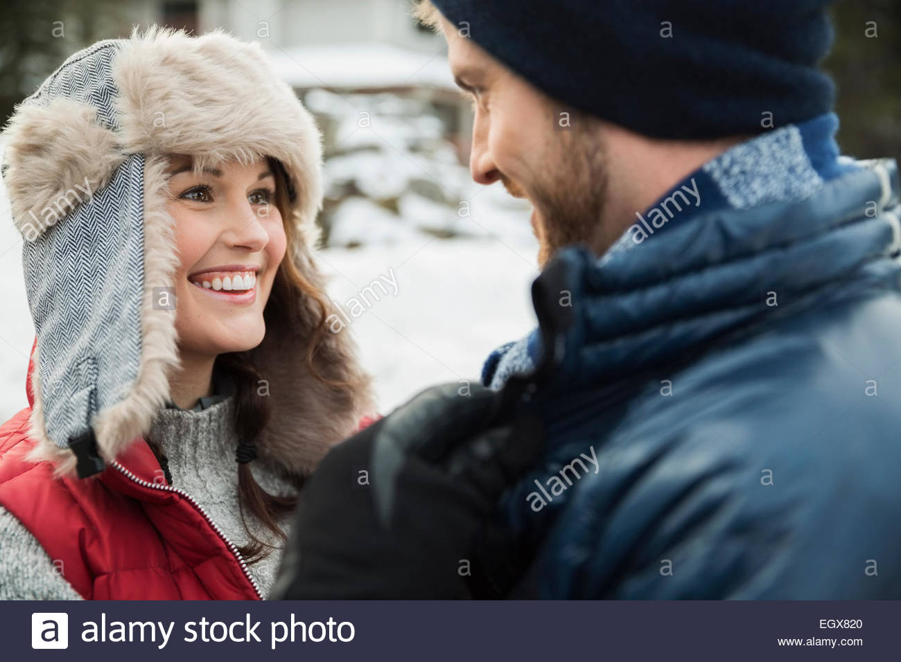 Couple in warm clothing smiling face to face - Stock Image