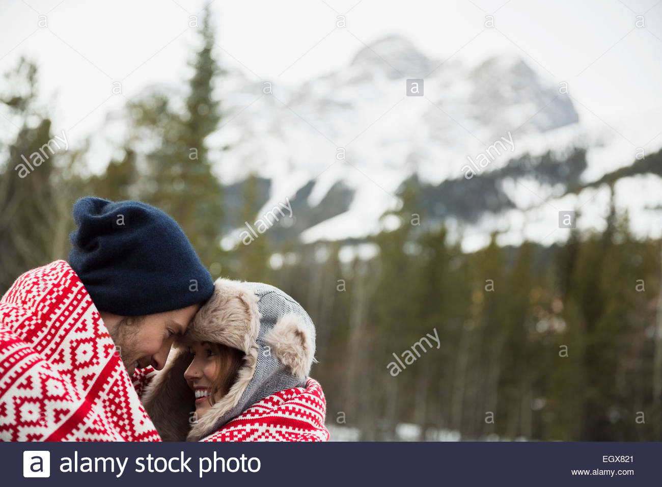 Couple wrapped in blanket below snowy mountain - Stock Image